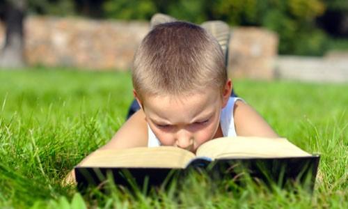 Παιδί διαβάζει βιβλίο στην εξοχή